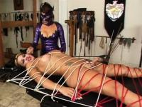 Fettered shemale slave suffers on a leather pad in her mistress's punishment room