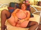 Redhead pregnant babe posing in stockings and fingering her pierced pussy