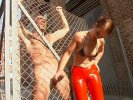 Bossy Euro bitch in red latex pants and bra grabs her dirty bald slave's cock and pulls it through a metal fence
