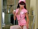 Busty redhead nurse Red in crotchless pantyhose posing on chair