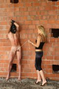 Beautiful mistress Irina humiliating masked slave in front of the brick wall
