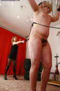 Cuffed and leashed slave gets his nipples pegged before taking a hardcore whipping from his mistresses